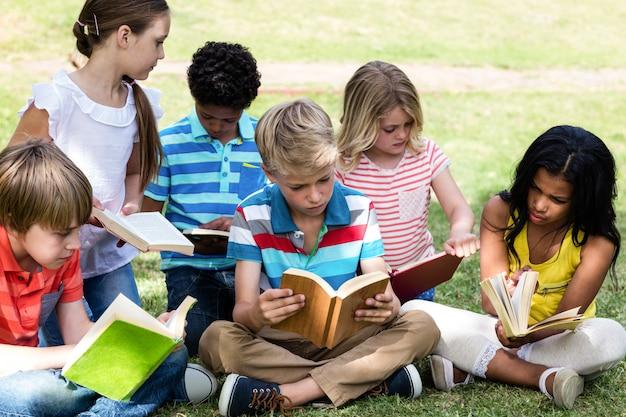 Dzieci, czytanie książki w parku
