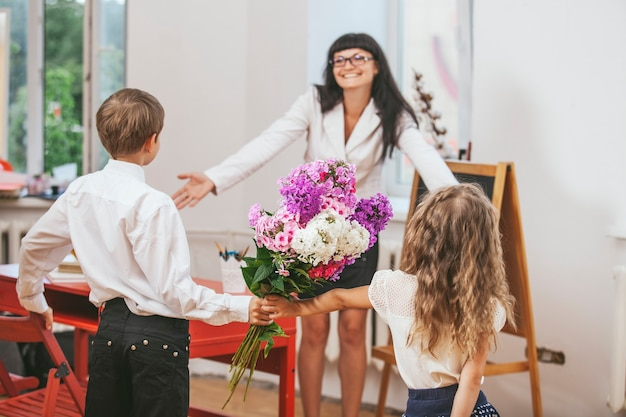 Dzieci dają kwiaty jako nauczycielka w dzień nauczyciela