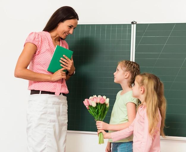 Dzieci dają kwiaty swojemu nauczycielowi