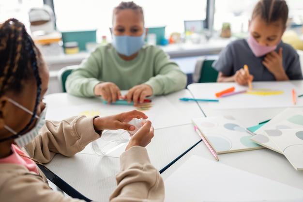 Dzieci dezynfekują ręce w klasie