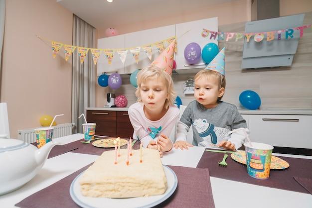 Dzieci dmuchanie świeczki na tort urodzinowy
