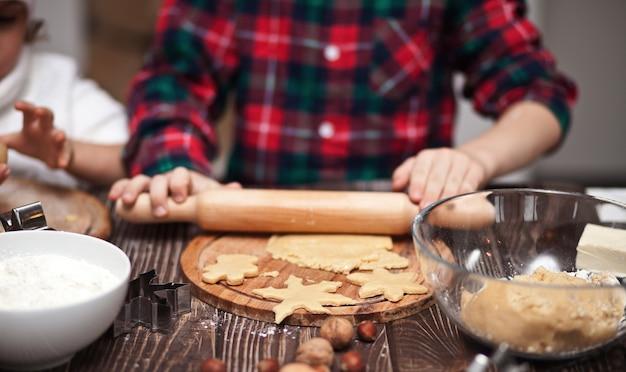 Dzieci do pieczenia ciasteczek świątecznych w domu w kuchni