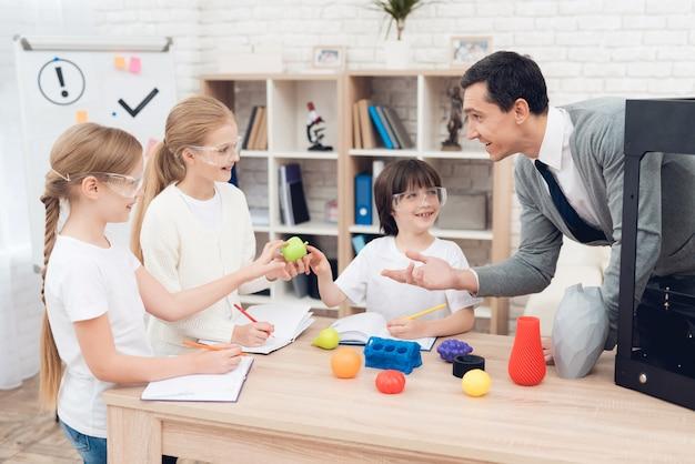 Dzieci drukują różne przedmioty w drukarce 3d z nauczycielem.