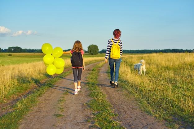 Dzieci dwie dziewczyny idące wiejską drogą z psem i balon, widok z tyłu