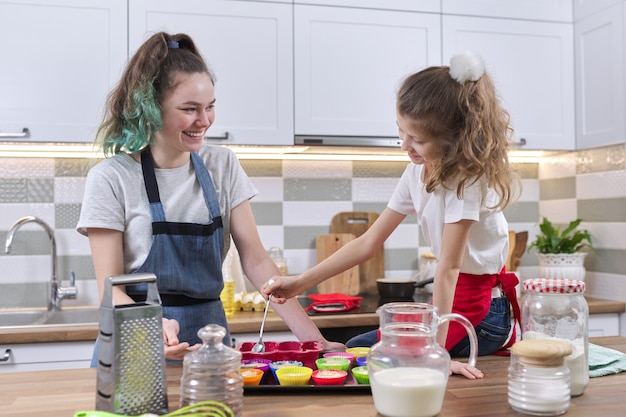 Dzieci dwie siostry dziewczyny przygotowujące babeczki w domowej kuchni. stara nastolatka z młodszym razem w kuchni. przyjazna rodzina, dobra zabawa, domowe wypieki, domowe życie