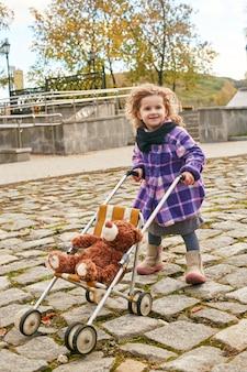 Dzieci dziecko w ubrania retro wiosna jesień. małe dziecko siedzi uśmiechnięte w naturze, szalik na szyi, chłodna pogoda.
