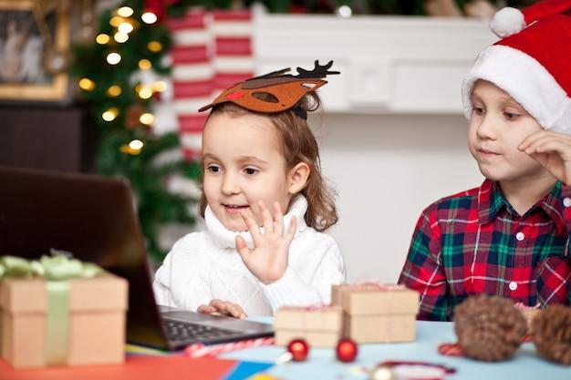 Dzieci dziewczyna i chłopak w czapce świętego mikołaja za pomocą notebooka laptopa cyfrowego tabletu.
