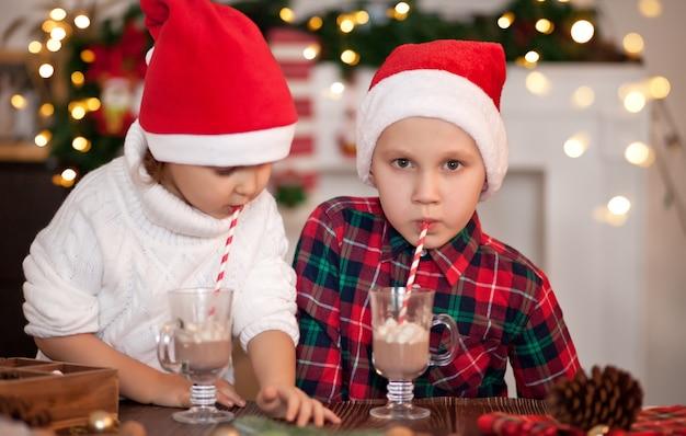 Dzieci dziewczyna i chłopak w czapkach mikołaja piją kakao z piankami.