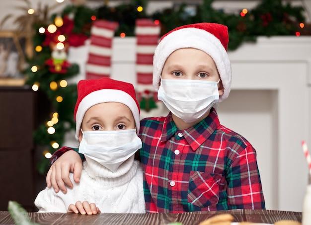 Dzieci dziewczyna i chłopiec w czapki mikołaja w maskach medycznych