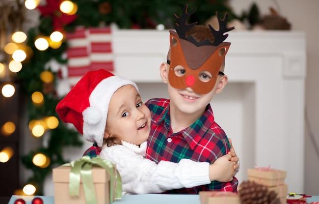 Dzieci dziewczyna i chłopiec w santa czapka i maska jelenia