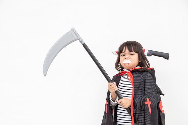 Dzieci dziewczyna ubrana w tajemniczą sukienkę na halloween, trzymającą sierp na białym tle
