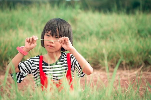 Dzieci dziewczynka bawi się na użytkach zielonych w ciągu dnia