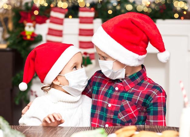 Dzieci dziewczynka i chłopiec w czapkach mikołaja w maskach medycznych gratulują sobie nawzajem wesołych świąt i szczęśliwego nowego roku i przytulają się.