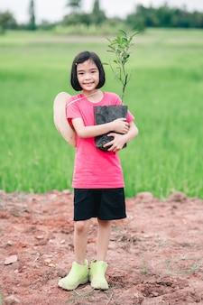 Dzieci dziewczynka trzymająca siew pomarańczy do sadzenia drzewa w ekologicznym ogrodzie uprawnym