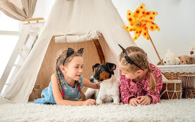 Dzieci dziewczynki leżące z psem foksterier w wigwam w domu