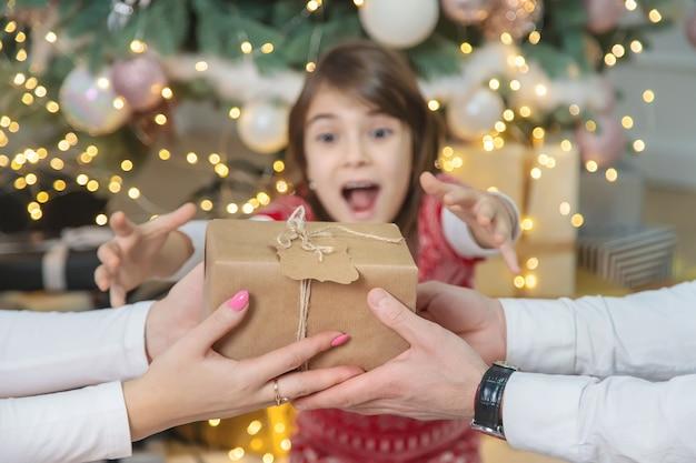 Dzieci-dziewczynki rodzice dają prezenty na boże narodzenie. selektywna ostrość. wakacje.