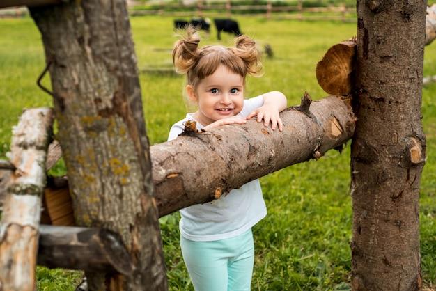 Dzieci, dziewczynki stojące przy płocie we wsi. spacery po okolicy. rolnictwo. ekologia i szczęśliwe dzieciństwo, piękna córeczka.
