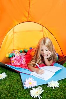 Dzieci dziewczyny writing notatnik w campingowym namiocie z kwiatami