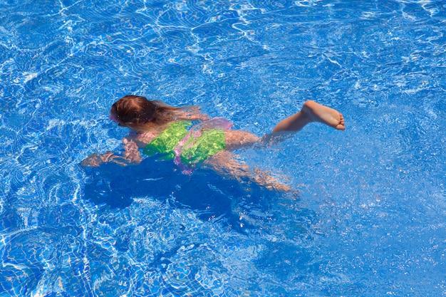 Dzieci gilr pływanie pod wodą w niebieskim basenie