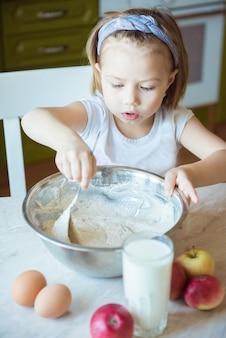 Dzieci gotowanie szczęścia kid home concept. dziewczyna wymieszaj ciasto