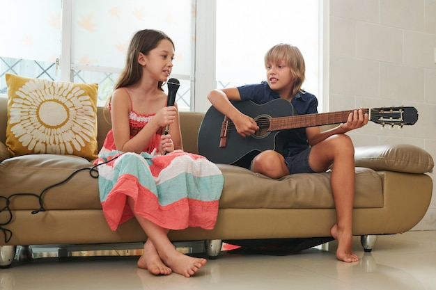 Dzieci grają na gitarze i śpiewają