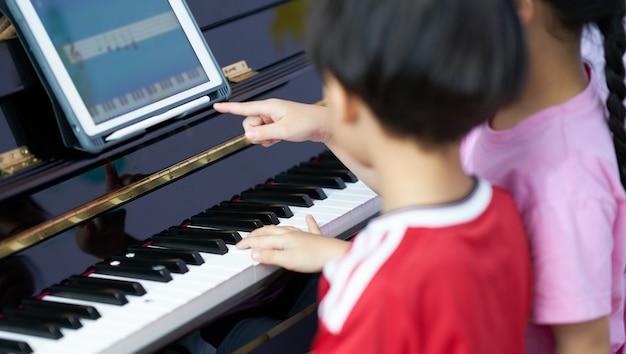 Dzieci grają na pianinie wraz z tabletem ucząc się edukacji domowej w internecie w kryzysie 19 lat