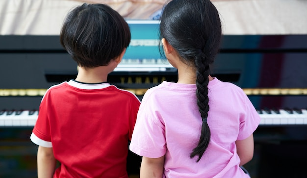 Dzieci grają na pianinie wraz z tabletem ucząc się w domu