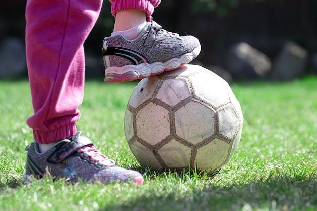 Dzieci grają w piłkę nożną na trawie, trzymają nogę na piłce. pojęcie gry zespołowej.
