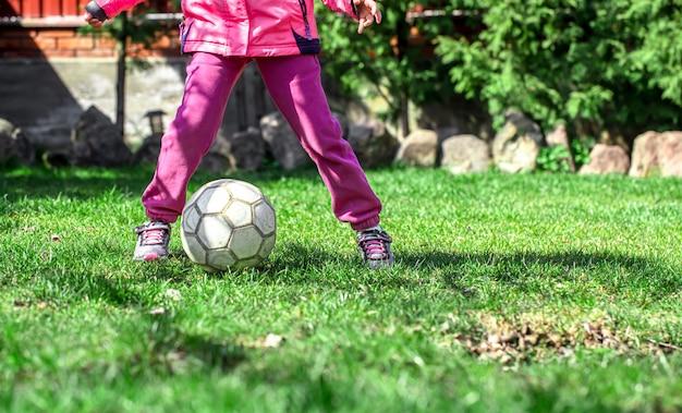 Dzieci grają w piłkę nożną na trawie, trzymają piłkę na nogach.