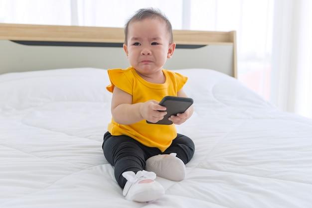 Dzieci grają w telefony komórkowe w łóżku