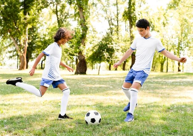 Dzieci grające w piłkę nożną na zewnątrz