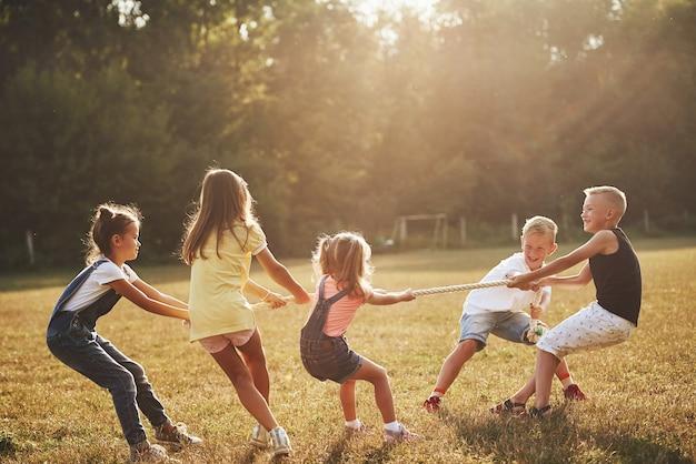 Dzieci grające w przeciąganie liny na pięknej łące w słoneczny dzień.