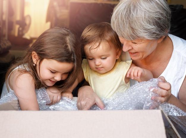 Dzieci i babcia otwierają pudełko. kobieta i wnuczki zaglądają do paczki