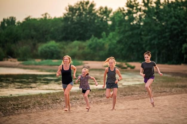 Dzieci i dorosłe dziewczyny biegają wzdłuż wybrzeża w strojach sportowych na tle przyrody o zachodzie słońca