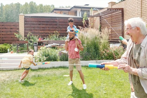 Dzieci i dorośli świetnie spędzają czas na podwórku strzelając z pistoletów wodnych