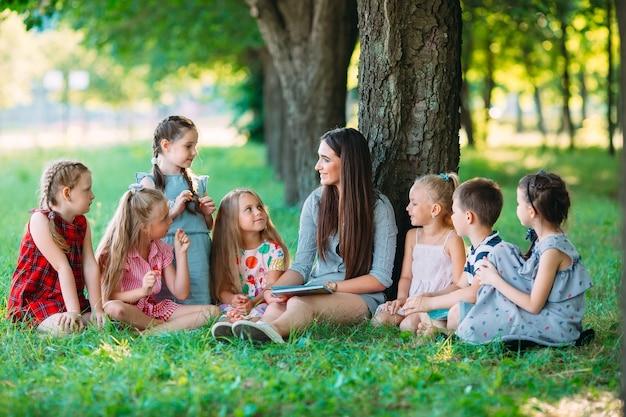 Dzieci i edukacja, młoda kobieta w pracy jako nauczyciel czytania książki do chłopców i dziewcząt w parku
