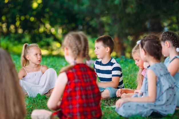 Dzieci i edukacja, młoda kobieta w pracy jako wychowawca czytająca książkę dla chłopców i dziewcząt w parku.