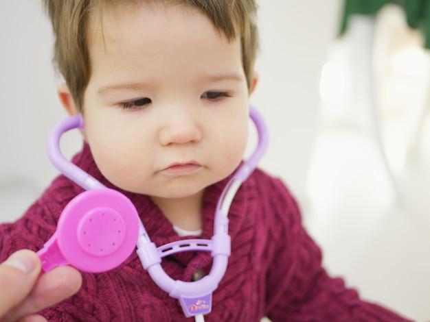Dzieci i fonendoskop. małe dziecko chłopiec z fonendoskopem bawić się lekarki. pojęcie opieki zdrowotnej i medycyny. fonendoskop zabawkowy.