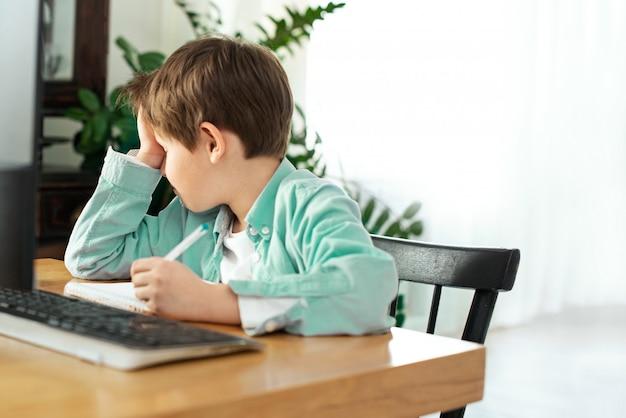 Dzieci i gadżety. uczenie się na odległość podczas izolacji w kwarantannie. chłopiec i laptop w domu. styl życia. blokowanie i dystans społeczny
