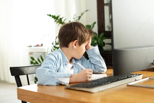 Dzieci i gadżety. uczenie się na odległość podczas izolacji w kwarantannie. smutny i zdenerwowany chłopiec z laptopem w domu. styl życia. blokowanie i dystans społeczny