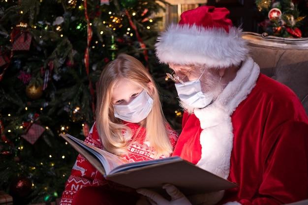 Dzieci i mikołaj w maskach medycznych. dziewczyna i święty mikołaj czytanie książki boże narodzenie siedzi w pobliżu bożego narodzenia