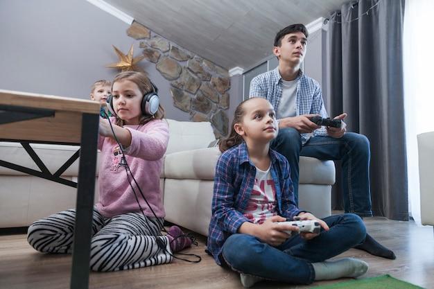 Dzieci i nastolatki grające w gry wideo w salonie