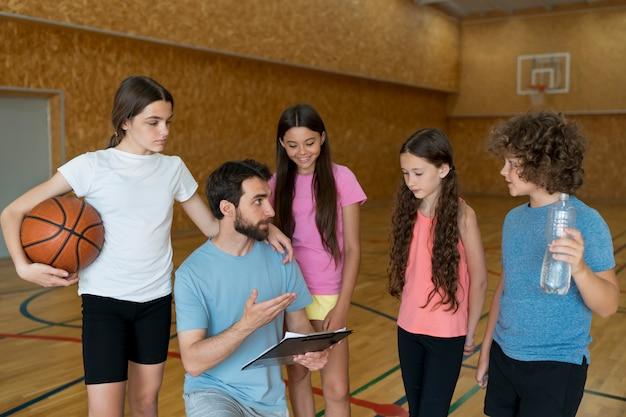 Dzieci i nauczyciel omawiają średni strzał