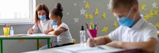 Dzieci i nauczyciel w maskach medycznych w klasie