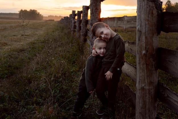 Dzieci i ojciec spacerują o zachodzie słońca po skoszonym polu