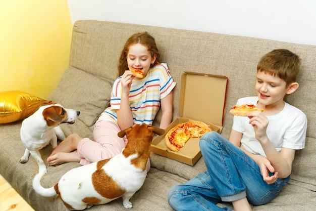 Dzieci i pies jedzą smaczną pizzę na kanapie w swoim domu.