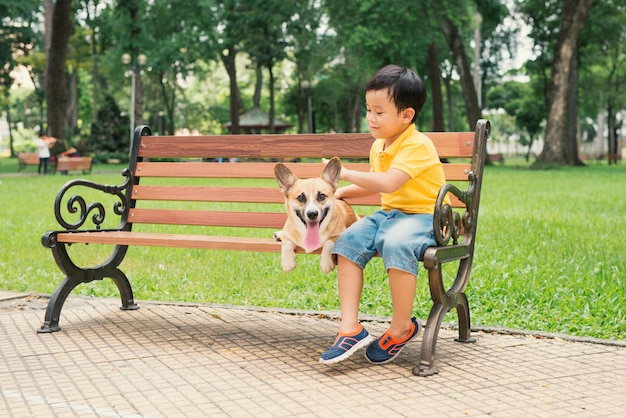 Dzieci i psy na zewnątrz. azjatycki mały chłopiec bawiący się i bawiący się w parku ze swoim uroczym pembroke welsh corgi.
