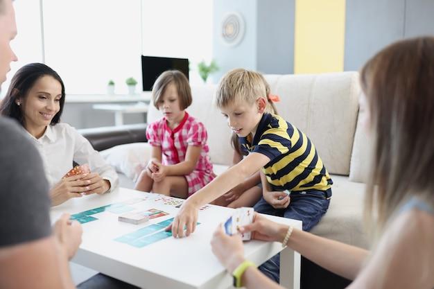 Dzieci i rodzice grają w gry planszowe w domu. koncepcja rodzinnego czasu wolnego razem