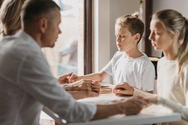 Dzieci i rodzice modlą się przed jedzeniem