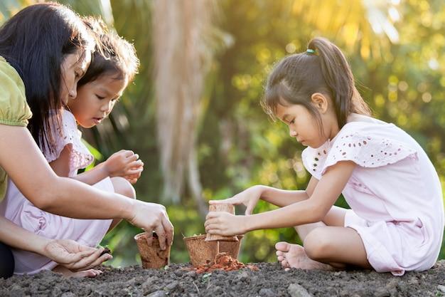 Dzieci i rodzice sadzą młode sadzonki w doniczkach z włókien z recyklingu w ogrodzie